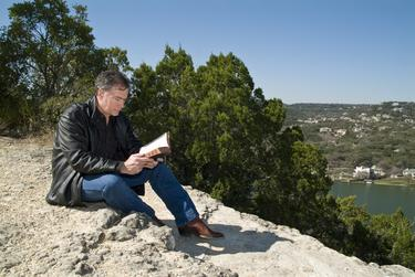 A man reading a Bible sitting outside.