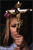 Little girl holding a large cross