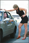 A man talking to a prostitute outside of his car.