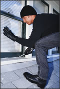 A man breaking into a home through a window.
