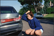 Teenage girl stares in grief at broken tail light of a car.