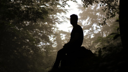 A man sitting on a rock.