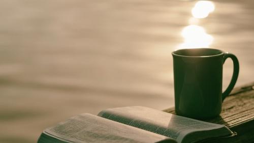 An opened Bible beside a coffee mug.