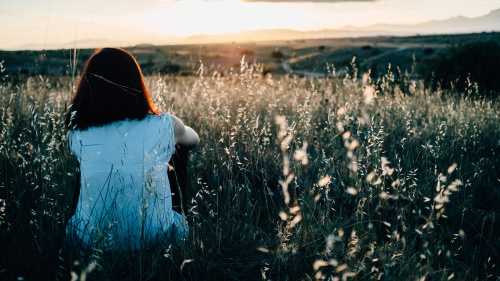 A young woman sitting in a field of grass and flowers watching the sunset.