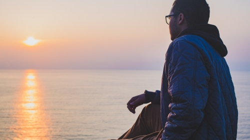 A man sitting by a body of water looking at the sunset.