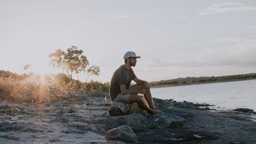 A man sitting on a log by a lake.
