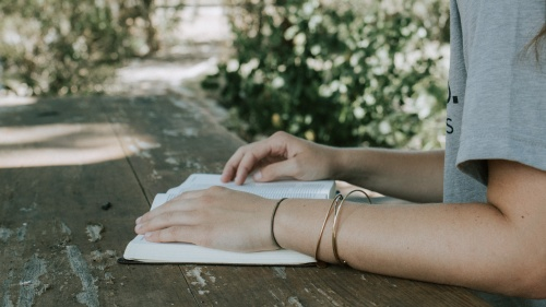 A young woman reading a Bible on a old table.
