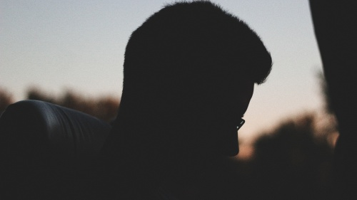 A silhouette of young man sitting in a bus.
