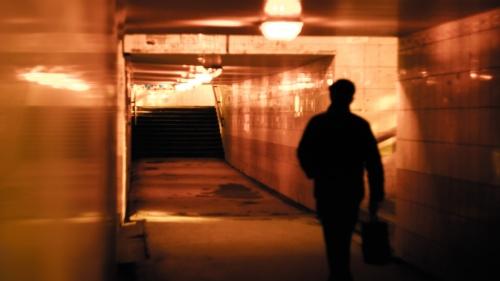 A man walking down a tunnel hallway.
