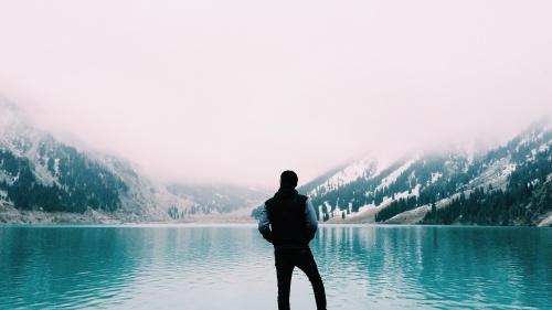 A man staring a clear blue lake.