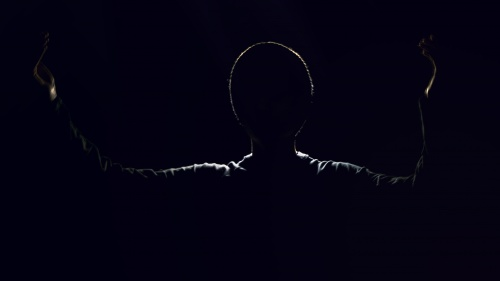 A shadow silhouette of a man with arms in the air.
