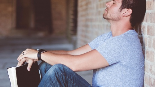 A man holding his Bible with his back propped against a wall - with eyes close and head down praying.