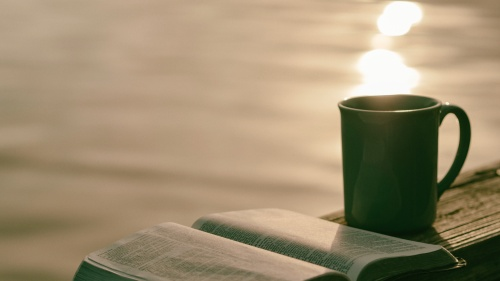 An opened Bible beside a coffee mug.