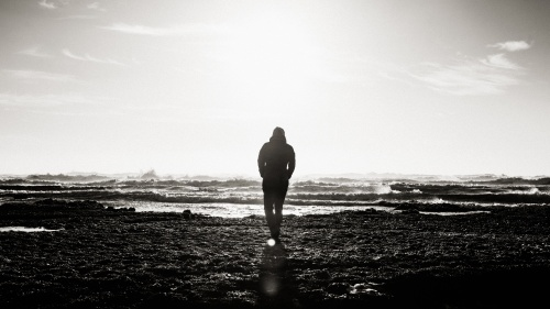 A silhouette of a person walking towards water.