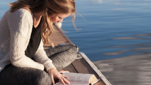 A young woman reading a Bible on a dock in the water.