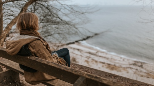 A woman sitting on a bench overlooking water.