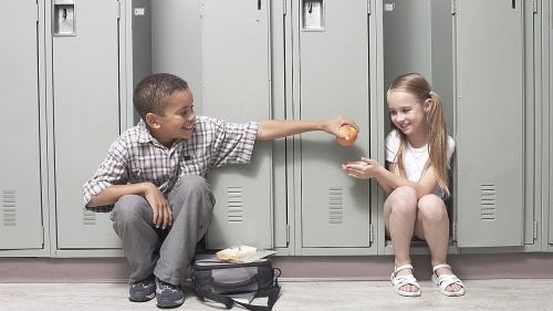 A young boy giving an apple to girl a school.