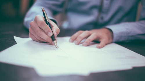 A man writing with a pencil on paper.