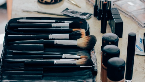 Makeup brushes, powder, lipstick on a table.