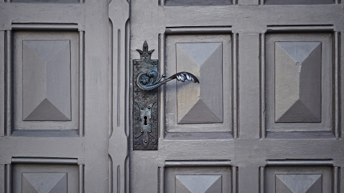 Old door with ornate handle and key hole.