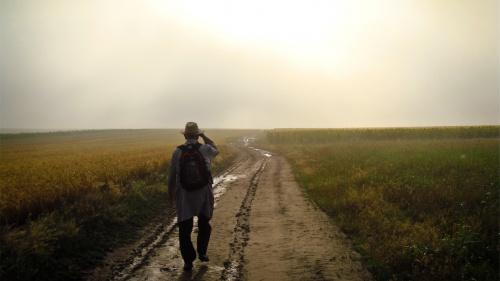 A man walking on a dirt path.