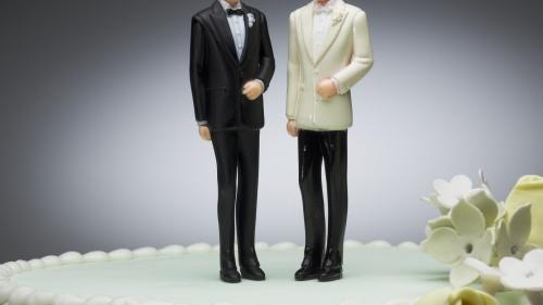 Two men figurines on wedding cake.