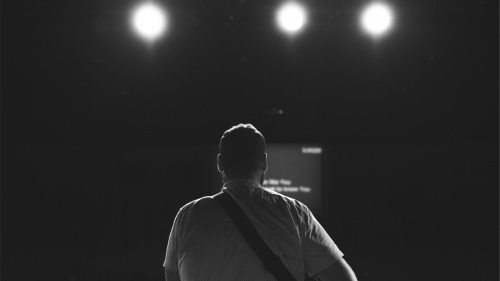 The back of a man looking at stage lights.