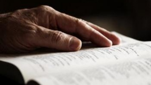An older person's hand on a Bible.