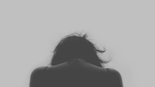 The back of a woman with her head down.