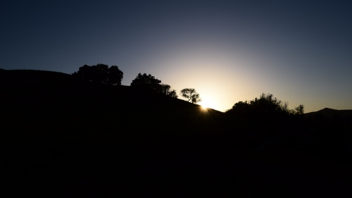 Sun coming over a hill.