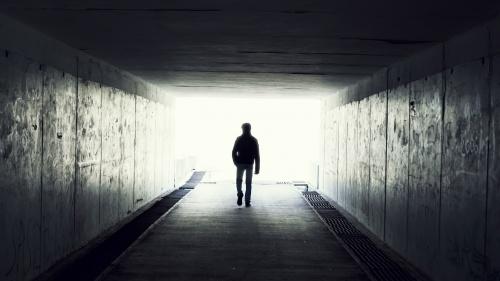 A man walking in a dark tunnel.