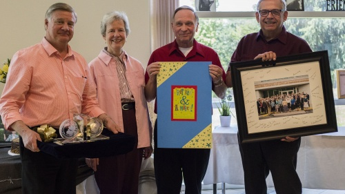 Peter Eddington, Media and Communications Services manager and Victor Kubik, president, award the Surratts with a card, keepsake bookends, and a photo of all home office employees that was also signed by employees.