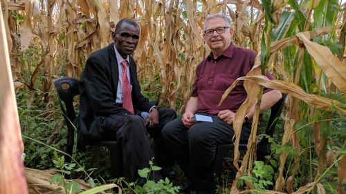 Filius Jere and Victor Kubik recording a podcast in a maize field.