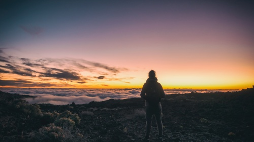 A woman on top of a mountain look out of over the clouds.