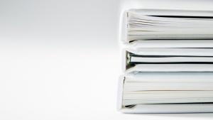 Photo of documents in stacked binders on white table.