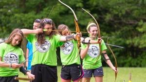 A girls dorm taking part in archery.