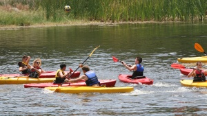 Campers kayak down the river.