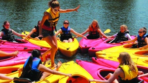 A picture of a group of campers in kayaks form a circle with the kayaks while one camper walks around the circle.