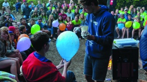 A photo of a camper holding a balloon while another camper paints it with shaving cream. The whole camp is watching in background.