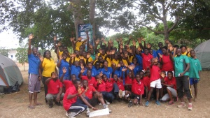 Campers and staff pose and wave at the camera.