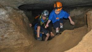 Campers explore a cave.