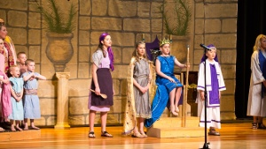 Right to left: the choir, Brooklyn Booth plays the narrator/palace cook, Cadence Phelps as Queen. Jedidiah, James Morris sits on his throne as Josiah, and Aaron Preston as Hilkiah.
