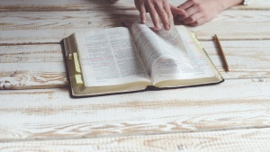 Photo of a marked up bible on a wooden table with a person's hands flipping through it. A pencil lays on the table next to the Bible.
