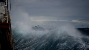 Photo of a stormy sea taken from a ship. The waves are crashing against the ship and the sky is filled with low gray clouds.