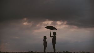 Photo of a girl holding an umbrella over another girl.