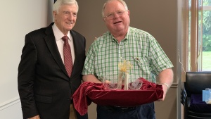 Dr. Ward presents Mr. Seelig with a gift in honor of his service as corporate secretary.