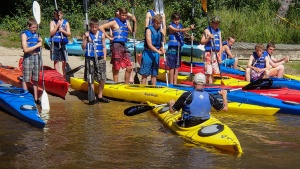 Campers getting ready to go on a kayak trip down the river.