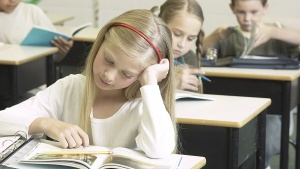 A girl looking at her school book.