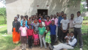 A group shot of the congregation in Mapoko. Behind them is the church building the brethern built.