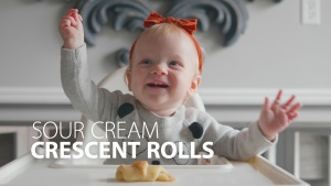 This is a photo of a baby holding the crescent roll.